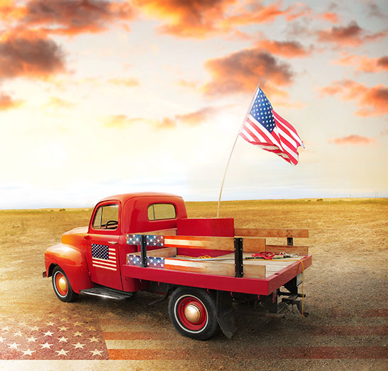 classic red pick up truck (circa 1940) with American flag attached to the back. Open field with beautiful skies. Patriotic image with classic or antique pick up shown. If you have a classic or antique vehicle that you need insurance for, call Odiorne Insurance today for a fast and friendly quote.