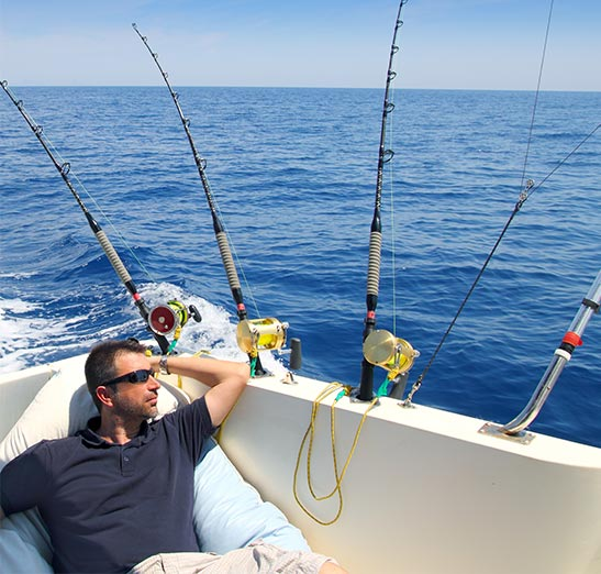 Boating Insurance Brandon Florida - man out on sea craft relaxing on sunny day while looking out at the sea with multiple fishing rods being used for trolling to catch fish.