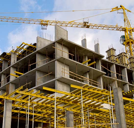 Multistory concrete building being constructed with large crane and metal scaffolding shown. The building is about 50% exposed to the air.