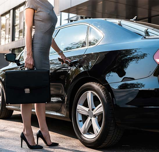 business woman getting in the backseat of a professional ride share or business limo service.