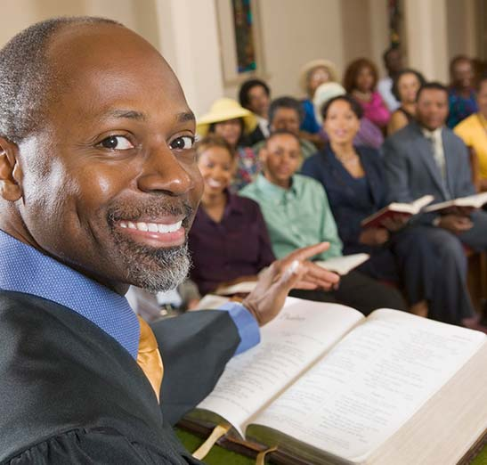Preacher wearing robe and smiling at the camera with Bible shown on lectern and parishioners sitting and listening.