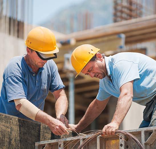 two male contractors working on a building outside