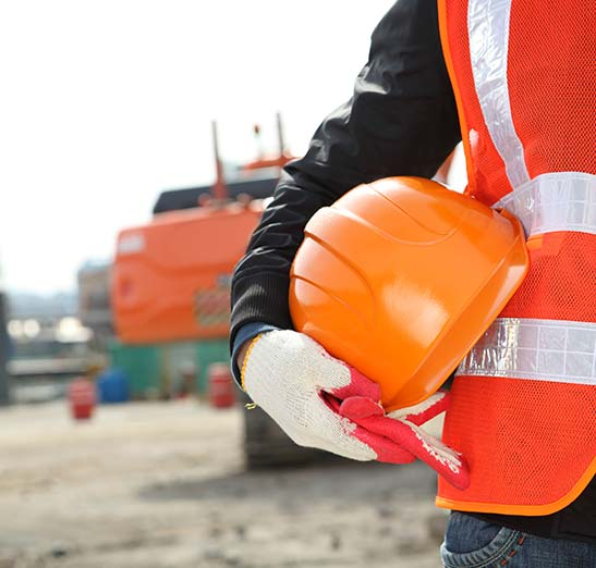outdoor construction site with closeup of a mans torso wearing a construction vest with a hardhat under his arm. There's a crane shown in the background slightly out of focus.