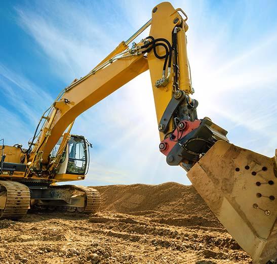 Large excavator construction equipment working in dirt field.