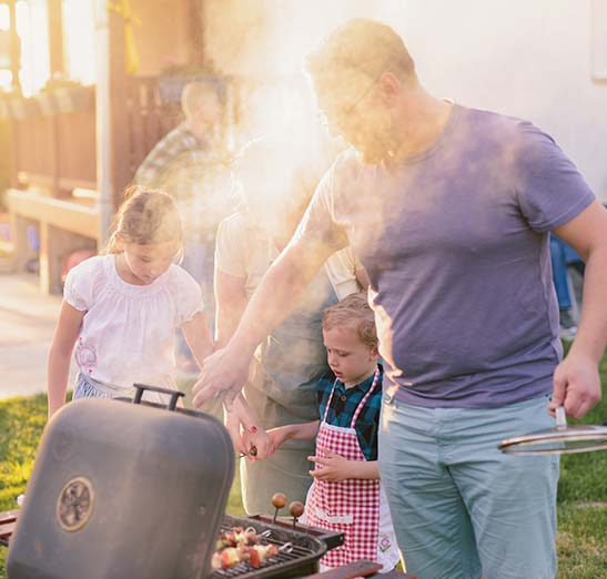 Family cooking outside with dad cooking shish kabobs while his wife and kids are standing a few feet behind him helping him to place something on the grill. Smoky outside, sunny day.