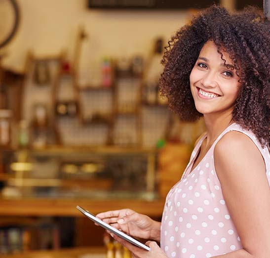 Attractive African American female business owner smiles at the camera while holding a tablet.