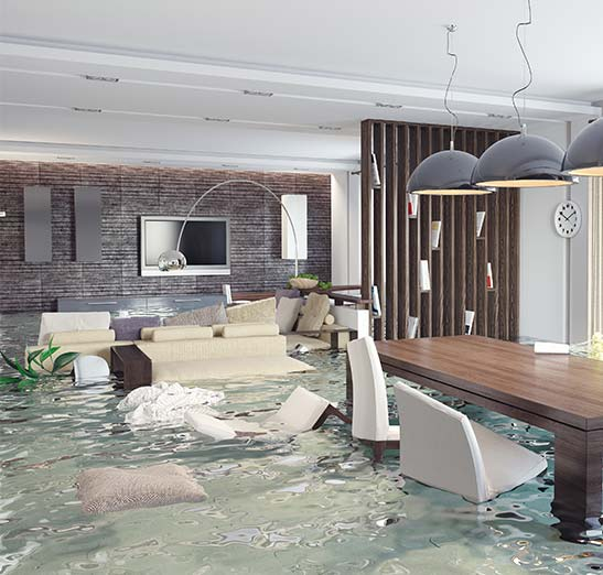 Interior of home flooding with water. Chairs and dinning are floating around. Serious water damage is shown in this house. Call Odiorne today for a competitive flood insurance quote.