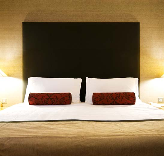 Fancy hotel bed with two classy red cylinder pillows. Warm light colors.
