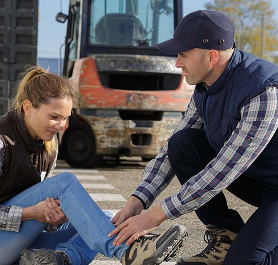 Injured female worker and concerned co-worker checking her ankle to see if she is able to walk.