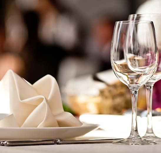 Image of a fine dinning table with wine glasses and flatware with napkin folded in a fancy way on dinner plate.