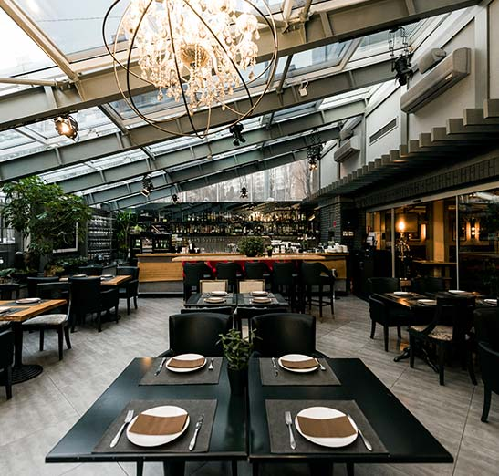 High end restaurant image. Expensive dinning. Classy empty restaurant displayed without customers. Artfully detailed dinning room with overhead glass ceiling exposing the city and sky.