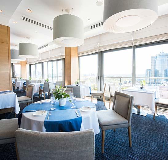 Fine dinning restaurant, blue carpet, sunny windows, fancy table setting, empty restaurant before customers arrive.