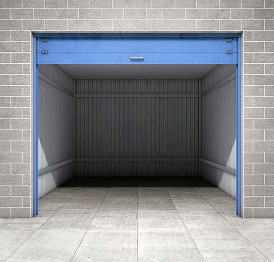 Empty self storage garage unit shown with the garage door open.