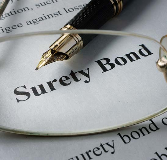 Surety bond graphic with pen and glasses on a contract shown in the graphic