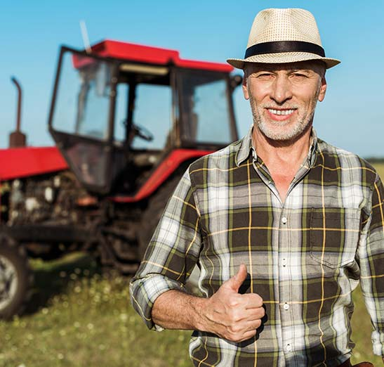 Smiling hat wearing farmer with thumbs up, flannel shirt, red farm tractor in the background